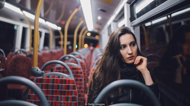 Young woman riding on a late bus in London